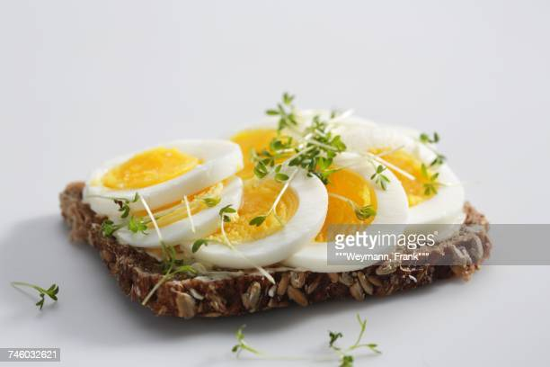 a slice of wholemeal bread topped with hard-boiled eggs and cress - hard boiled eggs stock photos and pictures