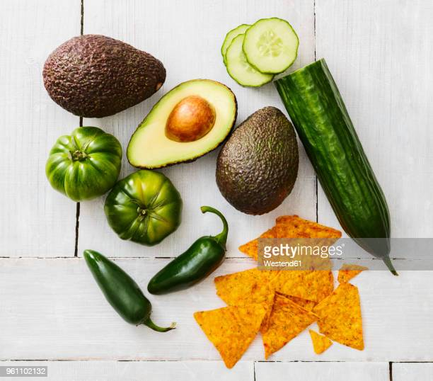 sliced and whole avocado, green tomatoes, jalapeno peppers, cucumber and tortilla chips - jalapeno stock-fotos und bilder