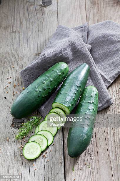 Sliced and whole cucumbers, dill, mustard grains and cloth on wood