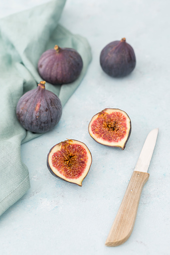 Sliced and whole fresh figs, kitchen knife and cloth - gettyimageskorea