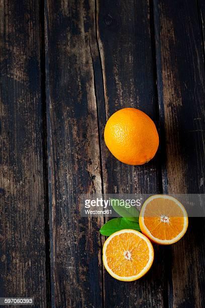 Sliced and whole orange on dark wood