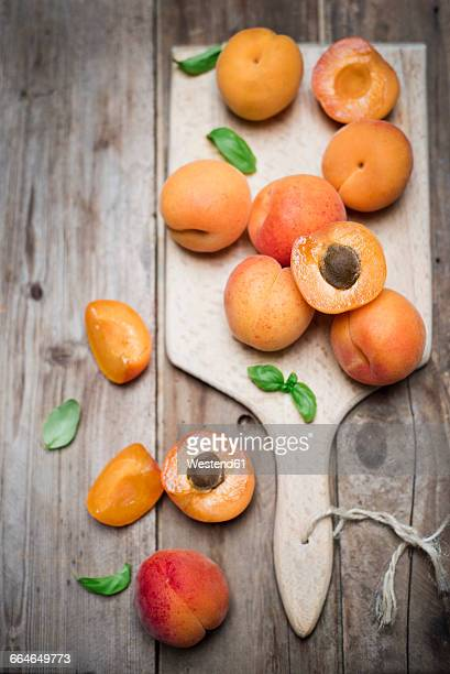 Sliced and whole organic apricots on wooden board