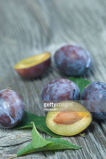Sliced and whole plums, Prunus domestica subsp. domestica, and leaves on grey wood