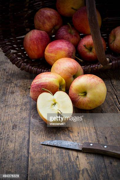 Sliced and whole red apples, basket and kitchen knife on wooden table