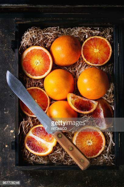 Sliced and whole Sicilian Blood oranges fruit in black wooden box with sawdust over dark background With vintage knife Flat lay