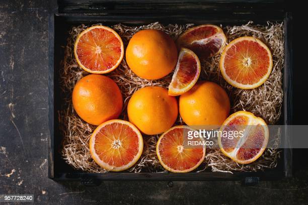Sliced and whole Sicilian Blood oranges fruits in black wooden box with sawdust over dark background Top view