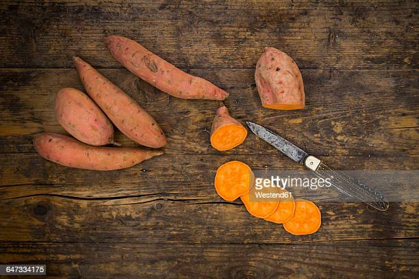 Sliced and whole sweet potatoes on dark wood
