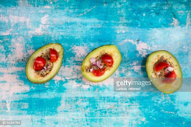 sliced avocado filled with quinoa, cherry tomatoes and red onion