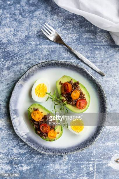 sliced avocado filled with red quinoa, tomatoes and eggs
