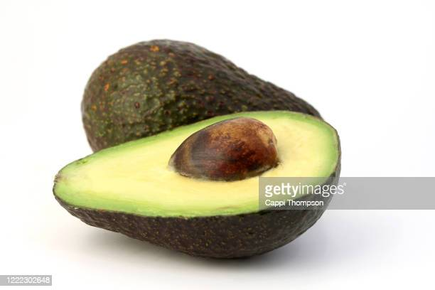 sliced avocado on white background - avocado stock pictures, royalty-free photos & images