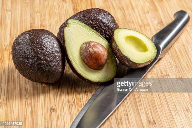 sliced avocado on wood - gunnar örn árnason stock pictures, royalty-free photos & images