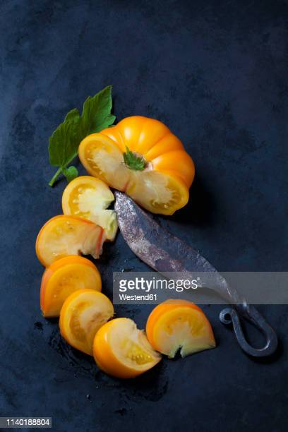 Sliced Azoychka tomato and an old knife on dark ground