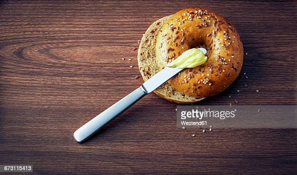 Sliced bagel with seeds, butter and a knife on dark wood