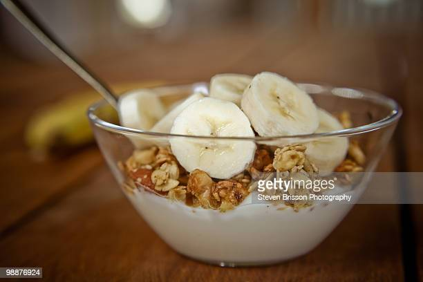 Sliced bananas, granola and yogurt in dish