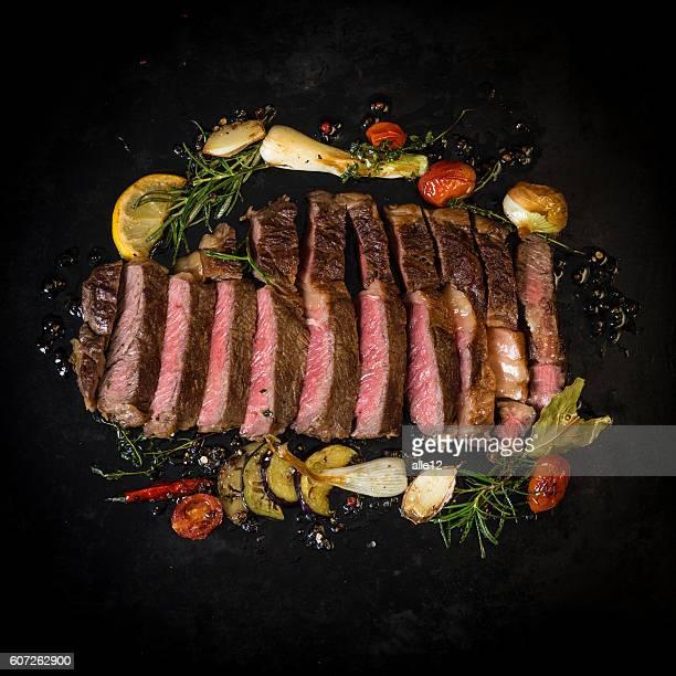 Sliced beef steak on dark background
