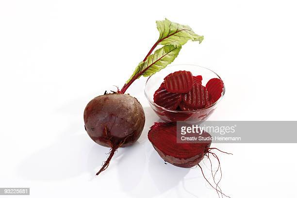 Whole and halved beetroot on white background, close-up