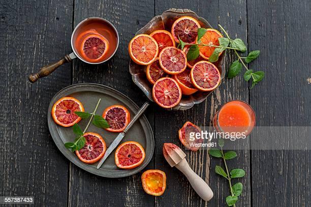 Sliced blood oranges and glass of blood orange juice on wood