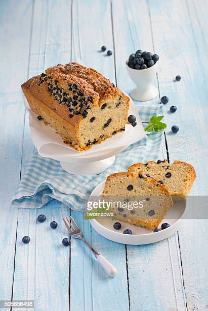 Sliced blueberry butter cake and fresh blueberries on blue wooden background.