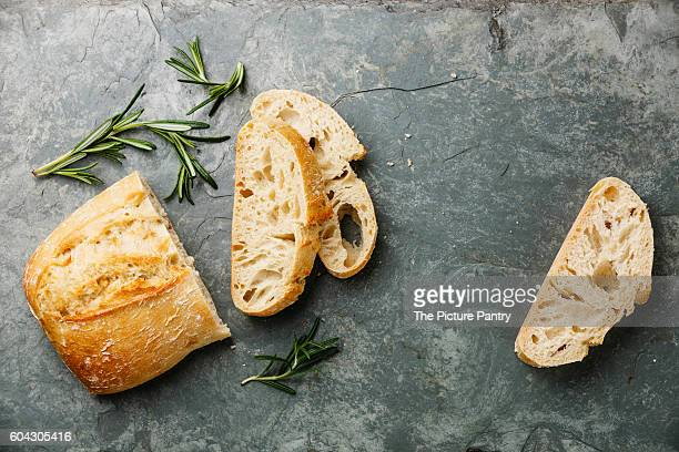 Sliced bread Ciabatta and rosemary on gray stone slate background
