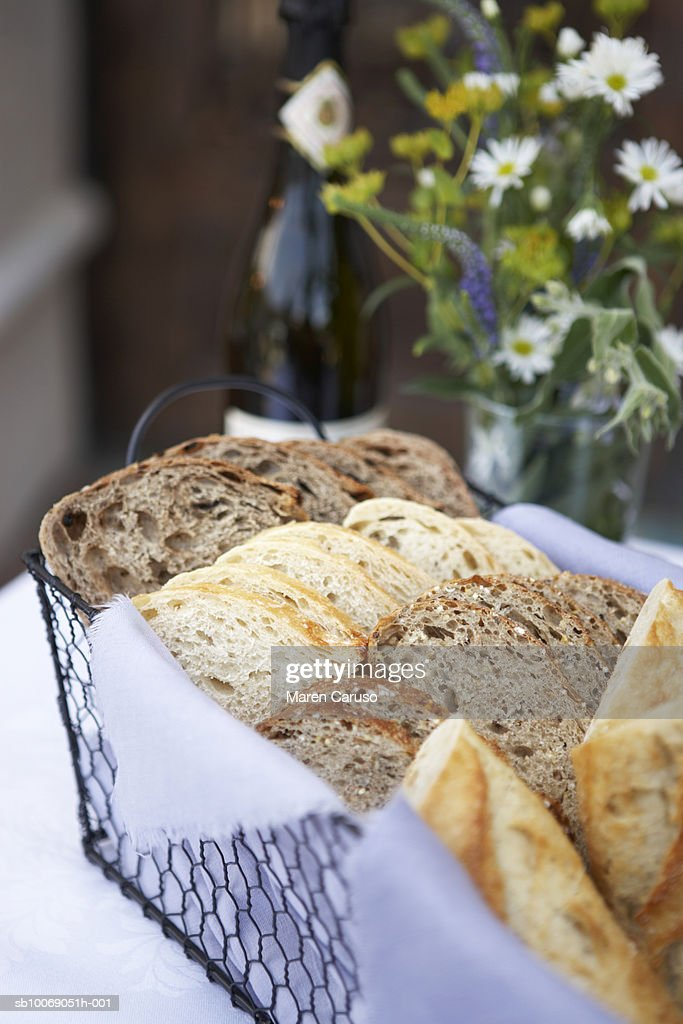 Sliced bread in basket with flowers in background, close-up : Stockfoto