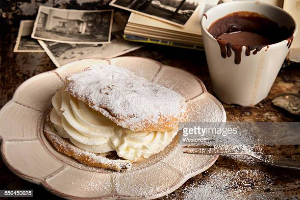 Sliced bun filled with whipped cream, cup of hot chocolate and old photographies