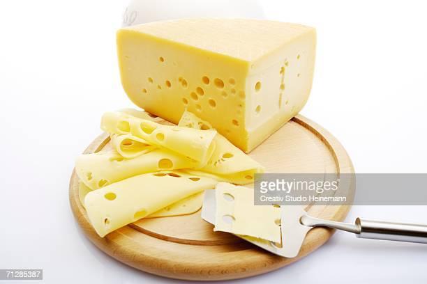 sliced cheese on chopping board - zwitserse kaas stockfoto's en -beelden