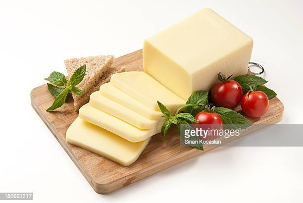 Sliced cheese, tomatoes and herbs in a cutting board