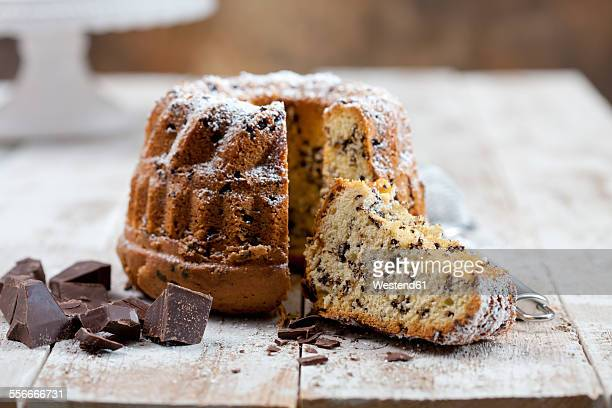 Sliced chocolate cake sprinkled with icing sugar and pieces of chocolate on wood