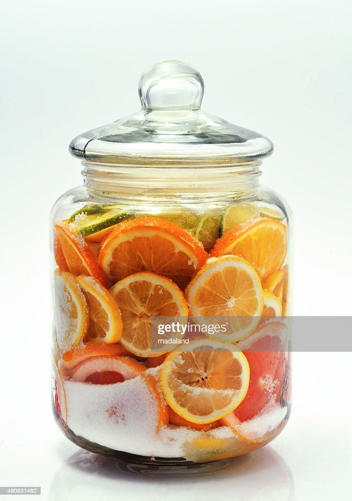 Scheiben Zitrusfrüchten in ein Gefäß geben. : Stock-Foto