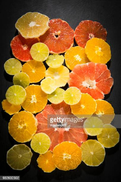 sliced citrus fruits on black ground - acid stock photos and pictures