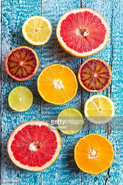 Sliced citrus fruits on light blue wood