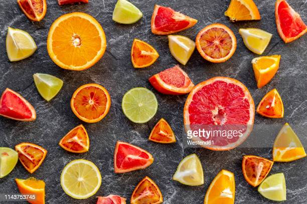 sliced citrus fruits on slate - citrus fruit stock pictures, royalty-free photos & images