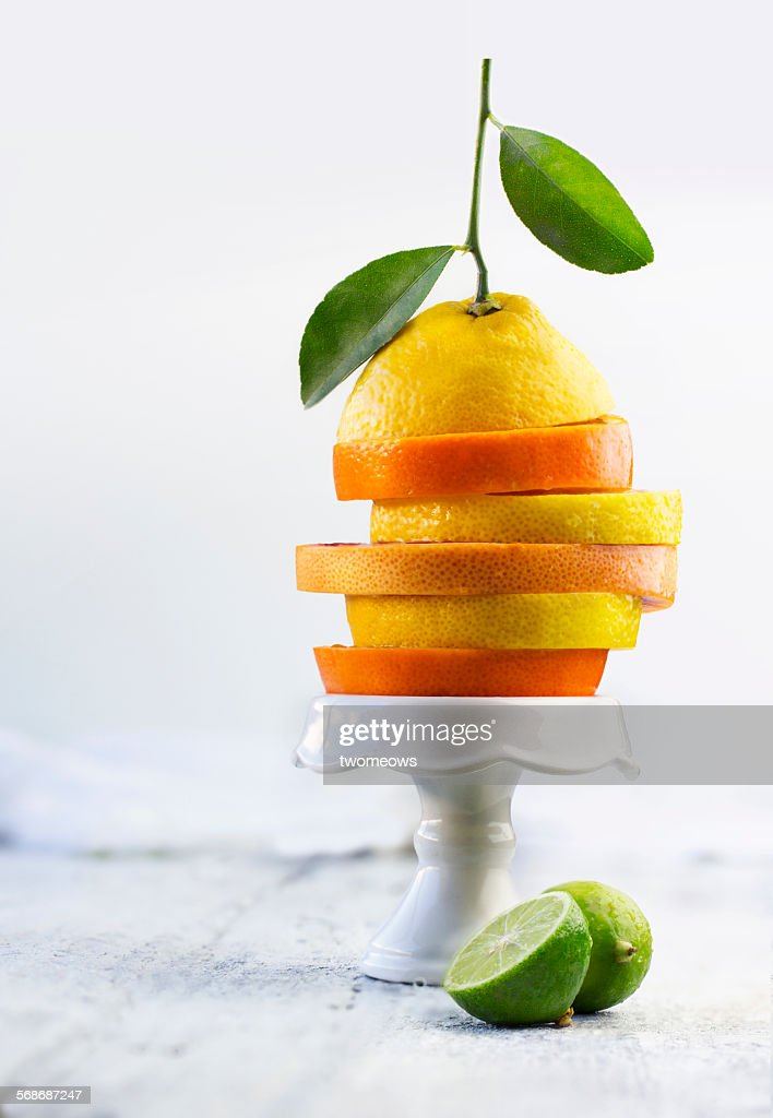 Sliced citrus fruits stacked up on cake stand. : Stock Photo