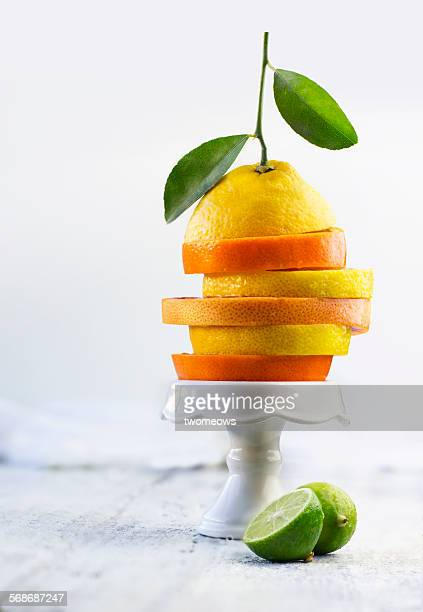Sliced citrus fruits stacked up on cake stand.