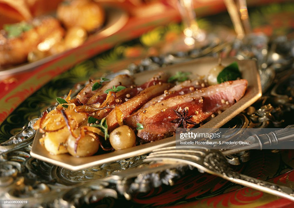 Sliced duck with caramelized onions on plate, close-up : Stockfoto