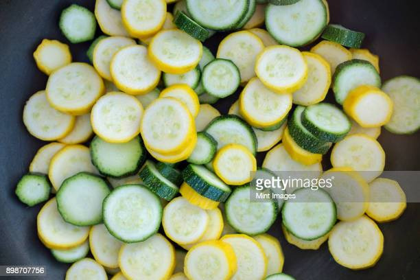 sliced fresh zucchini courgette vegetables with green and yellow skins in a frying pan. - zucchini stock pictures, royalty-free photos & images