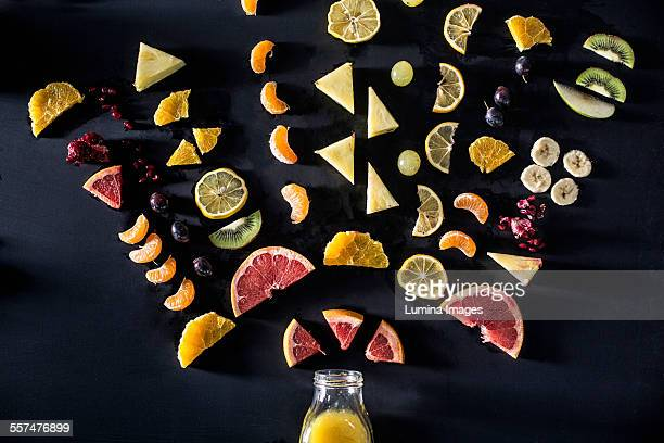 Sliced fruit arranged above juice bottle