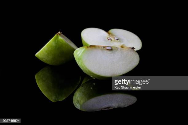 sliced green apple from side with reflection - ksu stock photos and pictures