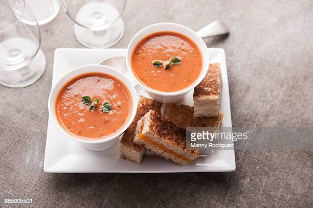 sliced grilled cheese sandwich and tomato soup - tomato soup stock photos and pictures