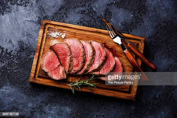 Sliced grilled tenderloin Steak roastbeef on wooden cutting board on dark background