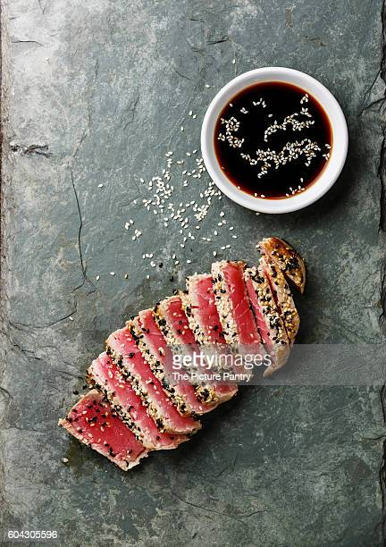 sliced grilled tuna steak in sesame and soy sauce on stone slate board - atún pescado fotografías e imágenes de stock