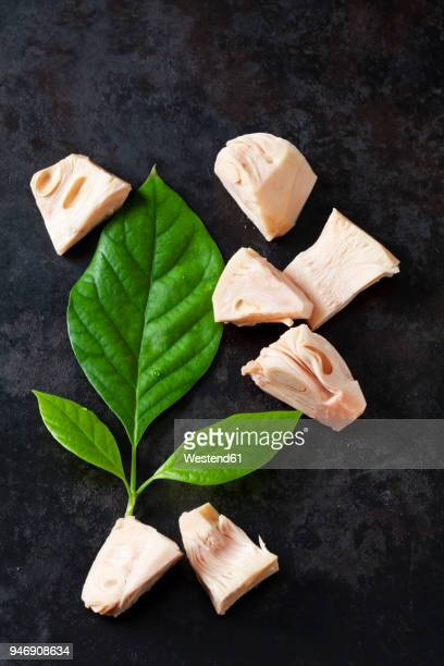 sliced jackfruit and leaf on dark ground - jackfruit stock photos and pictures