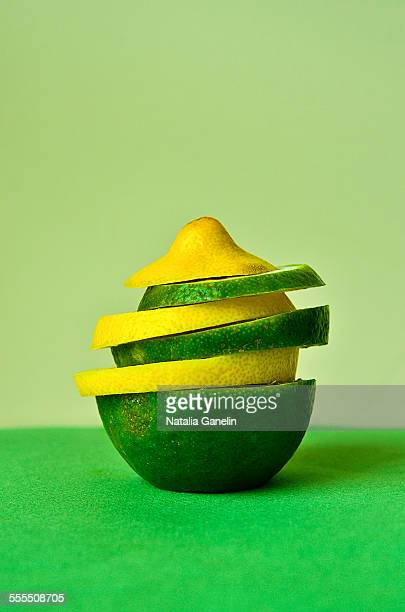 Sliced lemon and lime on green background