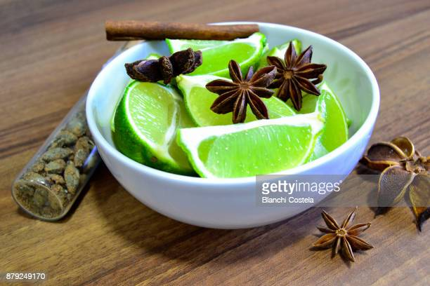 sliced lime in a white bowl with star anise - bittersweet berry stock photos and pictures