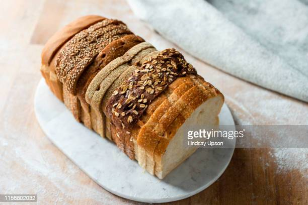 sliced loaf made up of variety of white and wholemeal slices on cutting board, high angle view - bread stock pictures, royalty-free photos & images