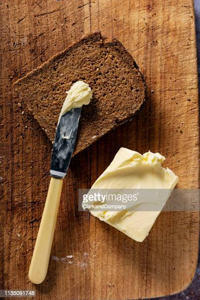 sliced loaf of organic rye bread with butter. - butter stock pictures, royalty-free photos & images