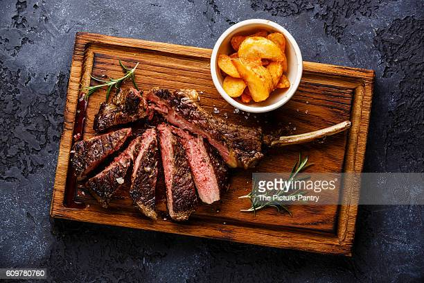 Sliced Medium rare barbecue Steak on bone Veal rib with potato wedges on dark background