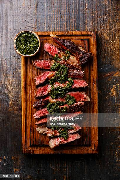 sliced medium rare grilled beef barbecue ribeye steak with chimichurri sauce on cutting board on dark background - チミチュリ・ソース ストックフォトと画像