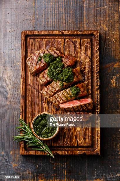 Sliced medium rare grilled beef Sirloin steak with chimichurri sauce on cutting board on wooden background