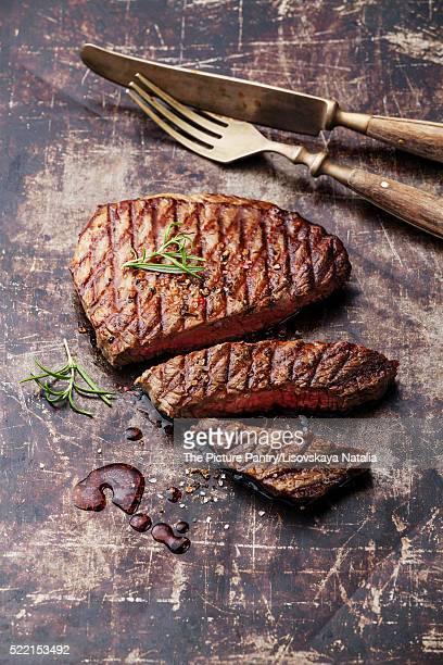 Sliced medium rare grilled Beef steak Ribeye on dark metal backg